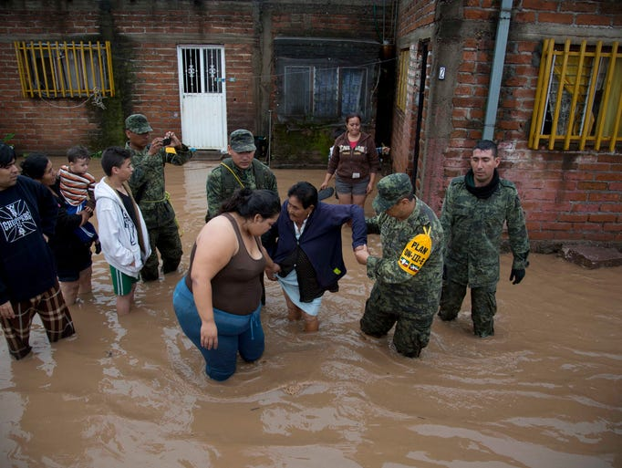 Soldiers help a woman to leave her flooded house to