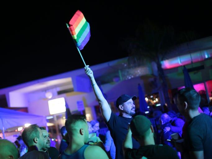 Paul Sprague of San Diego waves the Rainbow flag during