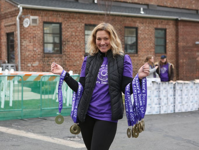 Volunteer Michelle Kavesh shows off the medals given