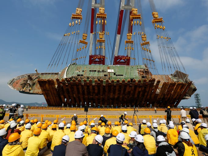 Relatives of Sewol ferry victims watch as the salvaged