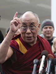 The Dalai Lama gestures as he talks to reporters outside