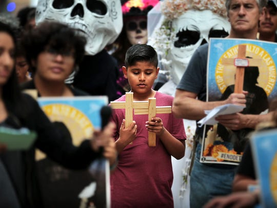Yandel Santos, 9, reads his mother's symbolic cross