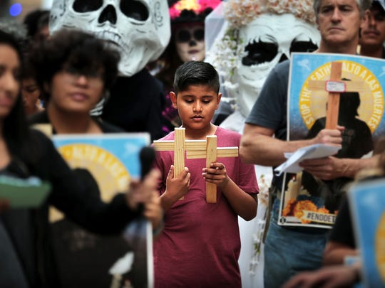 Yandel Santos, 9, reads his mother's symbolic cross as he joins sever immigrant rights groups in remembering immigrants who have died in detention during a vigil held in front of the Federal Building Sunday afternoon. Members of immigrant rights groups are demanding shut down of detention centers and an end of mass incarceration.