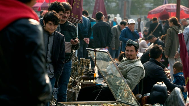 Uighur jade vendors sell their wares at an outdoor curio market where Chinese police have been checking their IDs everyday since a vehicle attack in Beijing on Oct. 28.