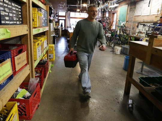Dan Baldi, a manager at the Des Moines Bike Collective, walks through the shop with a tool box on Thursday morning, Feb. 25, 2016, in the East Village.