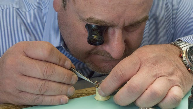 Steady hands and a strong magnifier are necessary to repair watches. Wael Mokhles works on a timepiece at his new shop, On Time Watch Experts, in downtown Plymouth.