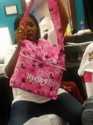 Karmeshia Pipes holds up a bag that bears the name
