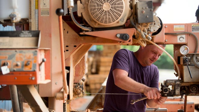 Josh Berry, a project manager at StoneMill Log & Timber Homes repairs a band saw at the company's wood mill on Tuesday, July 1.