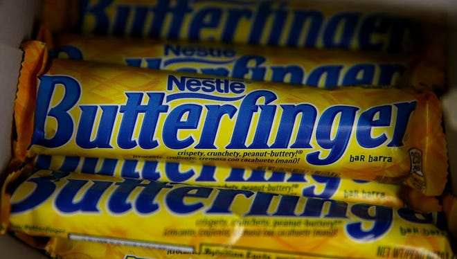 Nestle Butterfinger candy bars are displayed on a shelf at a convenience store Feb. 18 in San Francisco. Nestle USA announced plans to remove all artificial flavors and FDA-certified colors from its entire line of chocolate candy products, including the popular Butterfinger and Baby Ruth candy bars, by the end of 2015.