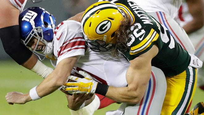 Green Bay Packers outside linebacker Clay Matthews (52) sacks quarterback Eli Manning (10) against the New York Giants at Lambeau Field.