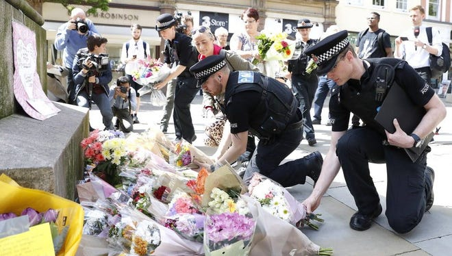 Police offices add to the flowers for the victims of Monday night pop concert explosion, in St Ann's Square, Manchester,  Tuesday May 23, 2017. A 23-year-old man was arrested in connection with Monday's Manchester concert bomb attack. The Islamic State group claimed responsibility Tuesday for the suicide attack at an Ariana Grande show that left over 20 people dead and dozens injured.