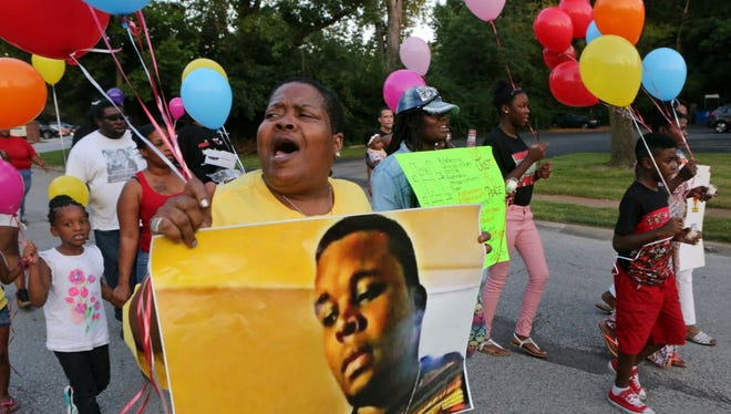 Sharon Cowan chants as she marches on the way to a candle light vigil to mark the two-year anniversary of the police shooting death of of Michael Brown in Ferguson, Mo. The family of Brown settled a federal wrongful death lawsuit with the city of Ferguson on Tuesday, June 20, 2017.