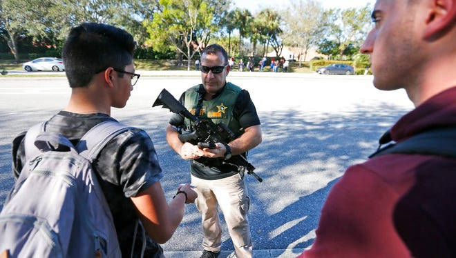 A law enforcement officer talks with students, Wednesday, Feb. 14, 2018, in Parkland, Fla. A shooting at Marjory Stoneman Douglas High School sent students rushing into the streets as SWAT team members swarmed in and locked down the building. Police were warning that the shooter was still at large even as ambulances converged on the scene and emergency workers appeared to be treating those possibly wounded. (AP Photo/Wilfredo Lee)