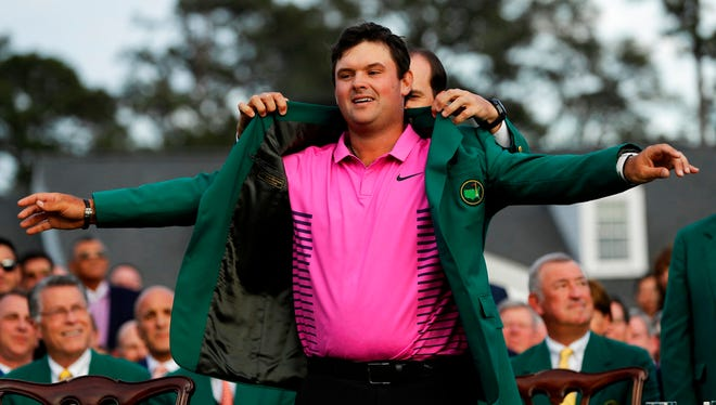 Former Masters champion Sergio Garcia, right, of Spain, helps Patrick Reed with his green jacket after winning the Masters golf tournament Sunday, April 8, 2018, in Augusta, Ga.