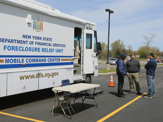 Area residents visit a New York State mobile Financial  Service Command Center, where residents can get assistance with homeowners insurance questions about flood damage.
