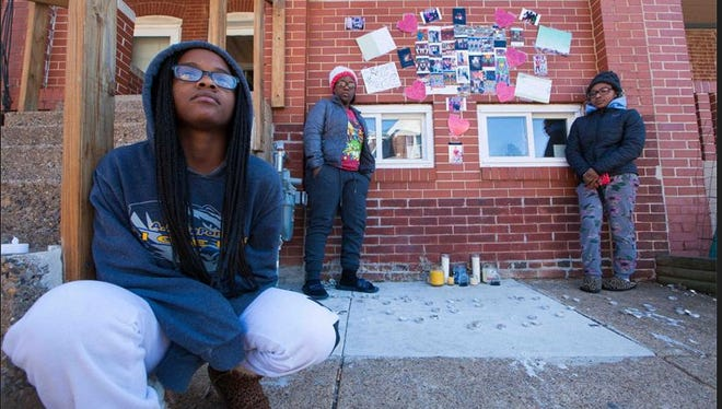 Sisters of Jordon Ellerbe, Jonaei Ellerbe (from left), 14, Jakiera Jordan, 19, and Jazmine Jordan, 21 stand in front of their home where a makeshift memorial of photos, messages and candles are display for A.I. duPont freshman Jordon Ellerbe, 16, who was shot and killed along North Broom Street.