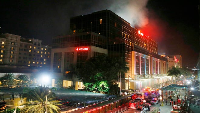 Smoke rises from the Resorts World Manila complex early Friday, June 2, 2017 in suburban Pasay city southeast of Manila, Philippines. Friday, June 2, 2017. Gunshots and explosions rang out early Friday at a mall, casino and hotel complex near Manila's international airport in the Philippine capital, sparking a security alarm amid an ongoing Muslim militant siege in the country's south.