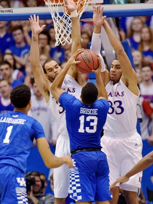 Jan 30, 2016; Lawrence, KS, USA; Kentucky Wildcats guard Isaiah Briscoe (13) shoots as Kansas Jayhawks forward Perry Ellis (34) and forward Landen Lucas (33) defend during the second half at Allen Fieldhouse. Kansas won the game 90-84 in overtime.