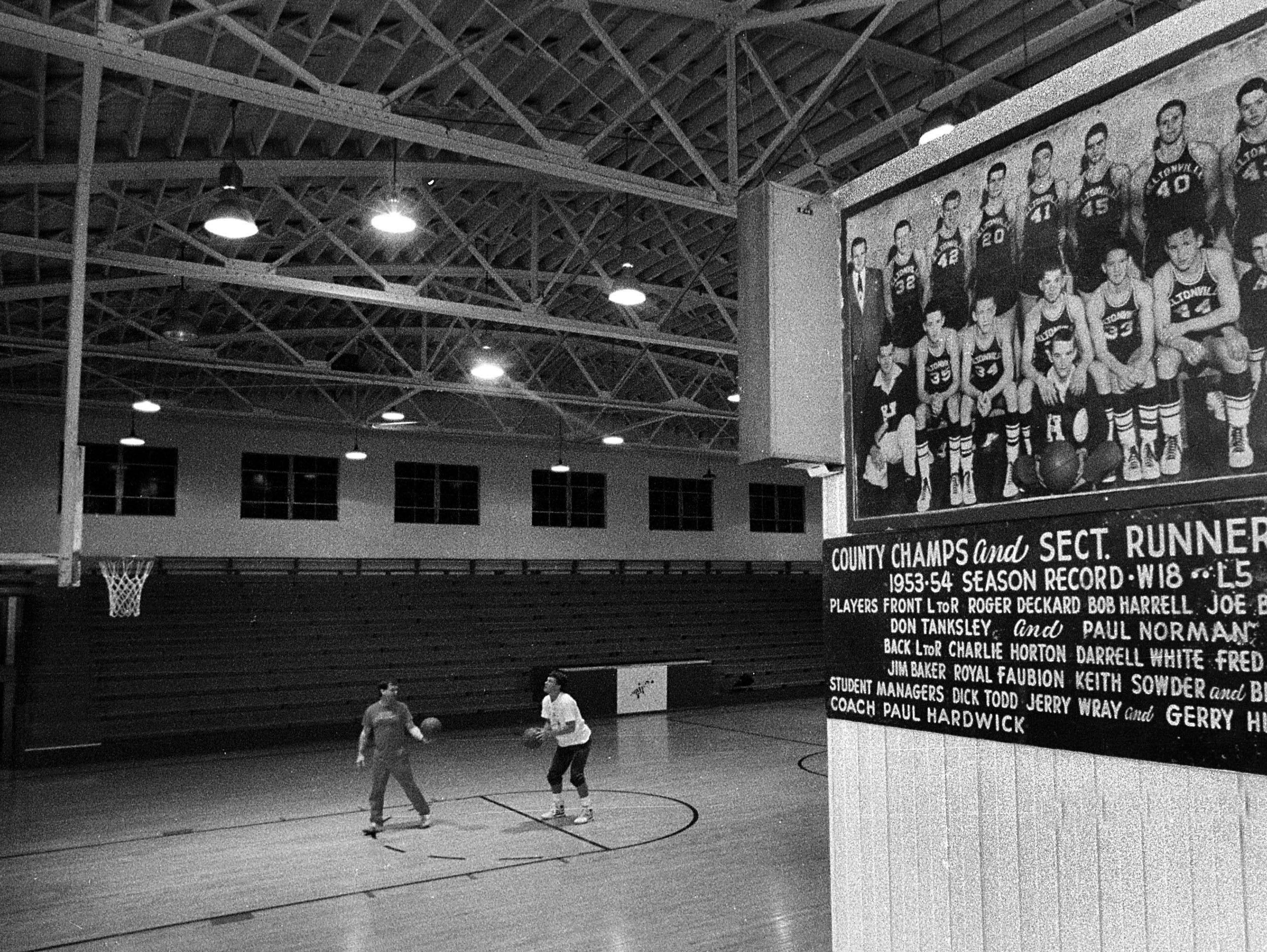 1990 Bedford North Lawrence senior Damon Bailey, right, practices his foul shooting at 6am in Heltonville at his old elementary school before going to his high school classes.