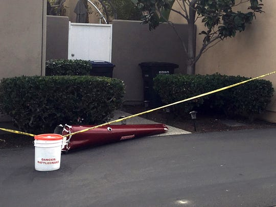 CORRECTS DATE TO JAN. 30, 2018 INSTEAD OF JAN. 25, 2018  A piece of a helicopter that crashed into a house in Newport Beach, Calif., is cordoned off by police tape Tuesday, Jan. 30, 2018. The four-seat Robinson R44 crashed shortly after takeoff at John Wayne Airport, killing several people and injuring a few others. (AP Photo/Amy Taxin)