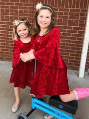Madison Barber, right, with her cast, her knee scooter, and her sister Sullivan