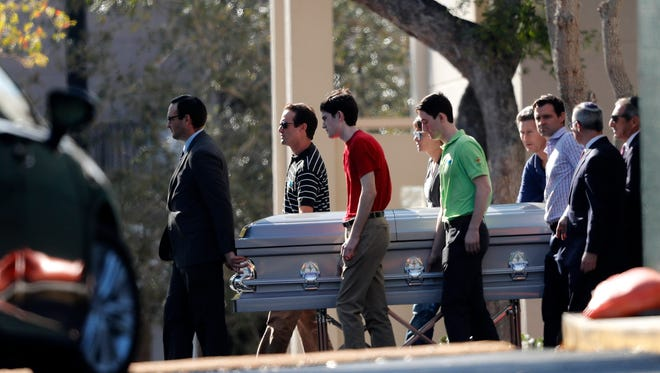 Pall bearers carry the casket of Scott Beigel after his funeral in Boca Raton, Fla., on Feb. 18, 2018. Beigel, a teacher at Marjory Stoneman Douglas High School in Parkland, was killed along with 16 others in a mass shooting at the school on Wednesday.  Nikolas Cruz, a former student, was charged with 17 counts of premeditated murder.