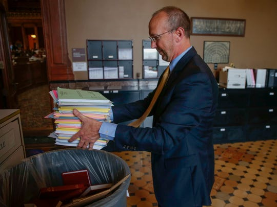 Representative Chip Baltimore (R-Boone) dumps a stack of papers into a recycling container on Friday, April 21, 2017, at the Iowa Capitol Building in Des Moines.