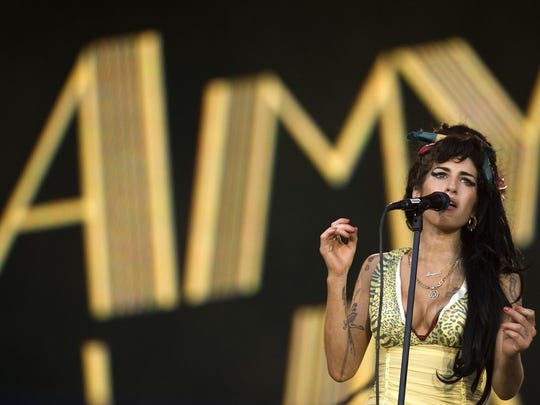 "FILE - In this file photo dated Friday, July 4, 2008, Jazz Soul singer Amy Winehouse, from England, performs during the Rock in Rio music festival in Arganda del Rey, on the outskirts of Madrid. A new movie entitled ""Amy"" directed by Asif Kapadia, is scheduled for release on Friday July 3, 2015. Critics love the movie and top performers sing the praises of the late Amy Winehouse, but the singer's father, Mitch Winehouse, says the film has been edited to depict the family as doing too little to help the ephemeral Amy Winehouse overcome addiction.(AP Photo / Victor R. Caivano)"