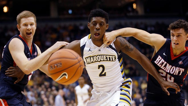 Marquette's Sacar Anim and Belmont's Taylor Barnette (20) and Burton Sampson go after a loose ball during the first half of an NCAA college basketball game Friday, Nov. 13, 2015, in Milwaukee.