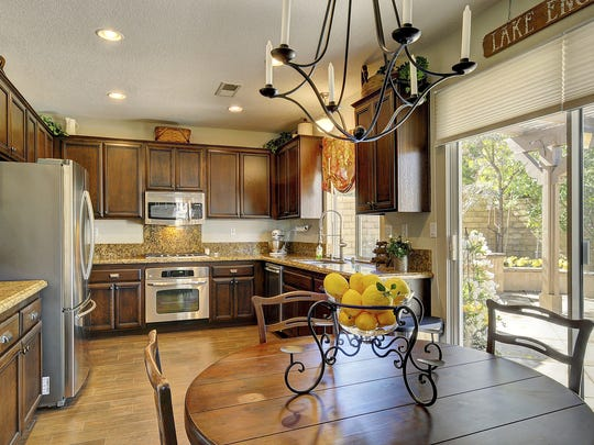 The great-room contains a breakfast area, sliding glass doors to the backyard and a gourmet kitchen featuring granite countertops, warm wood cabinetry and stainless steel appliances.