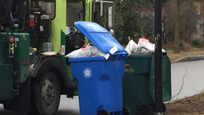 Overflowing blue recycling container that the city wouldn't take because it had trash in it, next to a full green garbage toter.