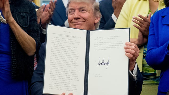 President Donald Trump holds up the Historically Black Colleges and Universities, HBCU, executive order after signing it Feb. 28 in the Oval Office.