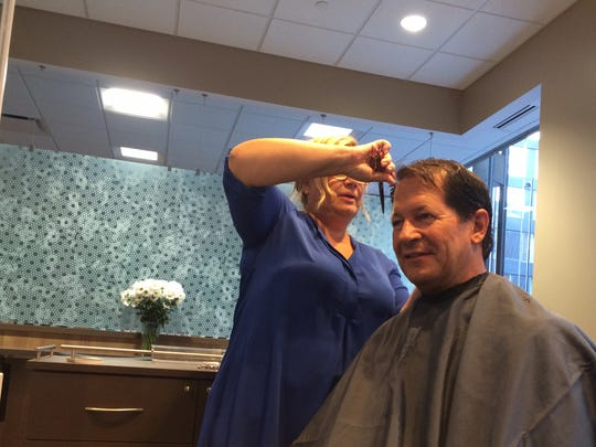 Paragon stylist Nancy Borin gives a haircut to Jim