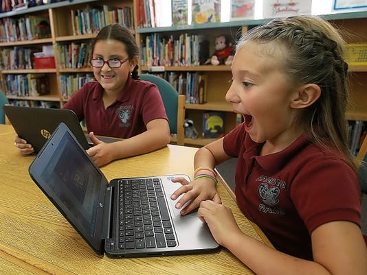 Ramona Elementary School second-grader Jazmin Barnes reacts as she learns to use the new computer that will be issued to her at the beginning of the 2015-2016 school year. Classmate Lauren Barraza is next to her.