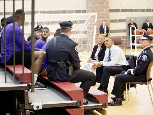 President Barack Obama, flanked by Camden, N.J. Police Chief J. Scott Thomson, right, and Camden Mayor Dana Redd, meet with local law enforcement and young people from the Camden community Monday at the Ray & Joan Kroc Corps Community Center, in Camden, NJ.