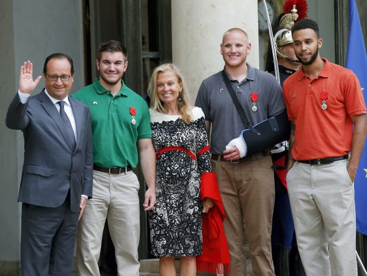 From the left, French President Francois Hollande, U.S. National Guardsman from Roseburg, Oregon, Alek Skarlatos, U.S. Ambassador to France Jane D. Hartley, U.S. Airman Spencer Stone and Anthony Sadler, a senior at Sacramento University in California, pose for photographers as they leave the Elysee Palace in Paris, France, after being awarded with the French Legion of Honor by French President Hollande, Monday, Aug. 24, 2015. French President Hollande and a bevy of officials are presenting the Americans with the prestigious Legion of Honor on Monday. The three American travelers say they relied on gut instinct and a close bond forged over years of friendship as they took down a heavily armed man on a passenger train speeding through Belgium. (AP Photo/Michel Euler)