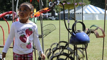 Erynn McCondichie, of Nashville, looks over some of the yard and garden creations by Jimmy Hopkins during the 35th Annual TACA Fall Craft Fair presented by the Nissan LEAF at Centennial Park Saturday, Sept. 28, 2013 in Nashville, TN.
