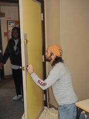 The Rev. Andrew Pomerville paints a door at the community center as part of the volunteer project at Edgewood Village.