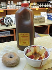Visitors enjoy cider, doughnuts and apple slices smothered in warm caramel sauce from Parmenter's in Northville.