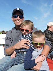 Tom Hinsman of Farmington Hills, with his son Everett on his lap and his son Michael sitting to the right, enjoy a tractor-pulled wagon ride at Plymouth Orchards & Cider Mill.