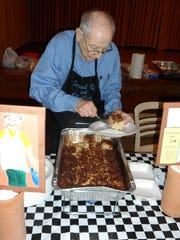 John Simon, a server at the Jewish Food Festival, scoops kugel, a type of casserole, on a plate.