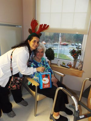 Roosevelt recreation therapist ELizabeth Wagner delivers one of the gifts to Roosevelt resident Helen Shapiola.