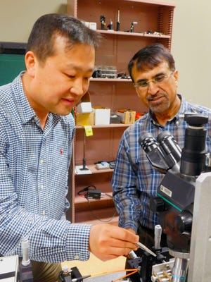 Engineering professors Sang-Yeon Cho, left, and Muhammad Dawood, right, examine an experimental setup of near-field imaging instrumentation in Cho's laboratory at NMSU. This setup will be used to measure the guiding properties of the optical circuit for their project.