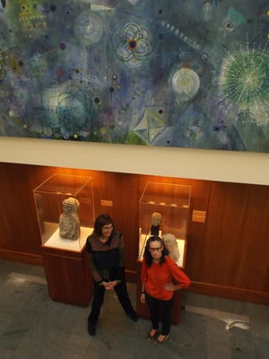 "Artist Laura Battle, left, and Mary-Kay Lombino, curator of the ""Touch the Sky"" exhibit at the Frances Lehman Loeb Art Center at Vassar College, stand below Battle's painting shortly after it was installed in the center's atrium gallery."