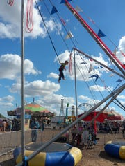 Steele Horaist flies into the air while riding the Power Jump at the Rapides Parish Fair on Sunday.