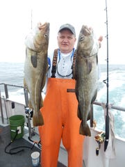Tommy Houk with a pair of codfish landed on the Point Pleasant Beach-based Voyager party boat on its three-day fishing trip to Nantucket.
