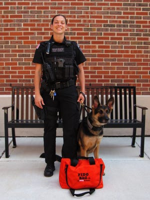 K-9 Niko and his handler, both of the Burlington County Sheriff's Department, pose with one of three Fido Bags the department was given by The Fetch Foundation.