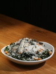 The kale caesar salad with lacinato kale, toasted hazelnuts, parmigiana reggiano, house caesar dressing and sardines, pictured, Tuesday, Oct. 31, 2017, at Harvest Pizzeria on Elm Street in Over-the-Rhine.