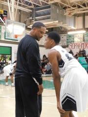 Northwest High boys basketball coach Chester Randell spends some time Thursday night with a player during the second half of the Raiders' first round basketball game with Eunice High.