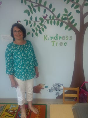 Emilie Blabac admires the kindness tree inside Mom's House. She volunteers for Mom's House as well as serving as a volunteer mentor for a pupil who attends Theodore Roosevelt Elementary School in Binghamton.